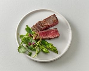 wagy beef on plate with greens